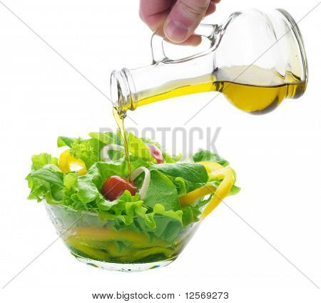 Healthy Salad and pouring olive oil over white