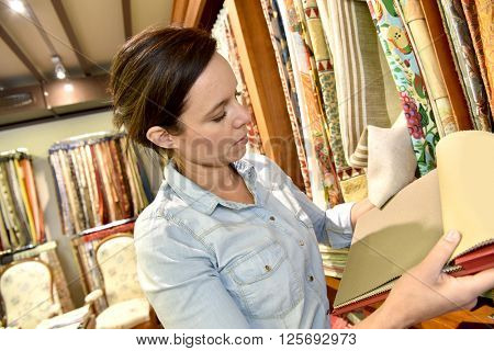 Woman in upholstery shop looking at samples