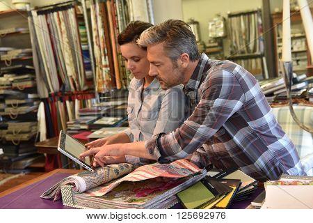 People in upholstery shop choosing sample