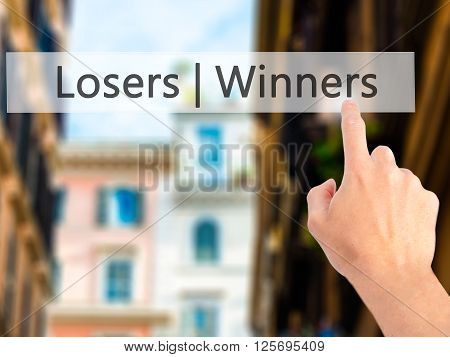 Winners  Losers - Hand Pressing A Button On Blurred Background Concept On Visual Screen.