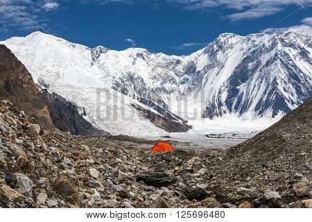 One Red Camping Tent Located on Rock Moraine of Giant Glacier in High Altitude Mountains with Peak Range Summits on Background Sun Blue Sky Clouds