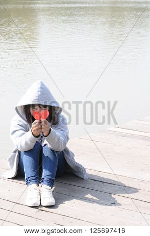 Sad Girl Praying to Reconcile with Red Broken Heart