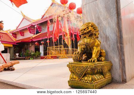 Golden chinese lion guardian sculture in front of the gate to the temple