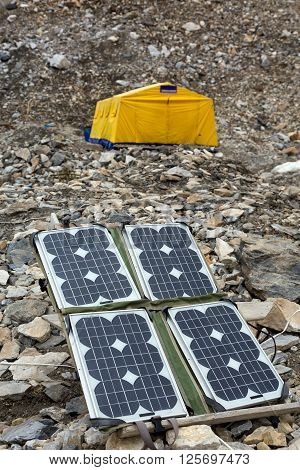 Solar Battery on Rocky Glacier Moraine for Electricity Supply of Sport Mountain Expedition in Wilderness Country with Large Yellow Tent on Background