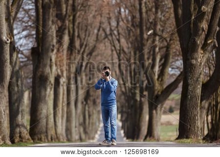 Photographer at work on the road between the rows of trees spring time