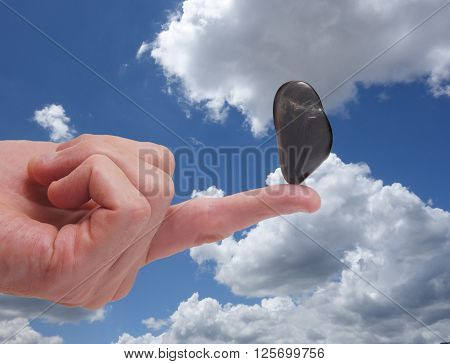 Stone balancing on a finger over blue sky background