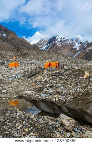 Mountain Expedition Camp on Glacier Moraine with Large Ice Crevasse and Melting Lake Foreground Clothing Hanged on Tent for Drying after Rain