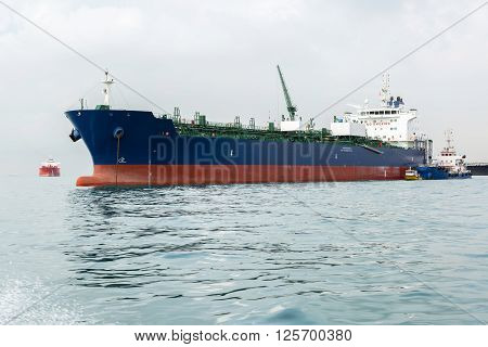 Blue and red ship in the sea while calm weather during bunkering operation.
