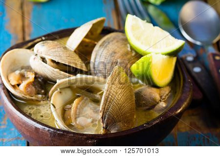 Seafood soup of clams in clay bowl on wooden blue background.  Mariscal or paila marina