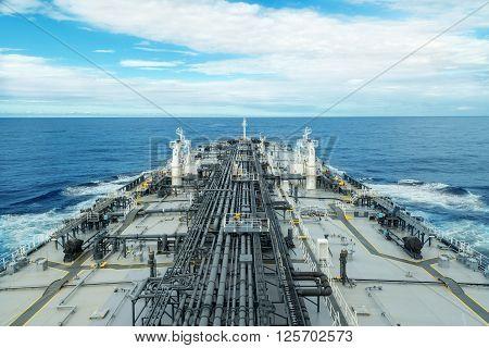 Grey and white tanker proceeding through blue sea under sky