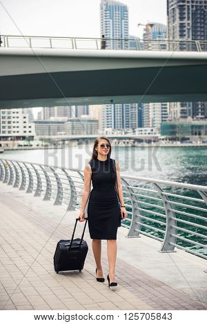 Elegant attractive business woman carrying her luggage.