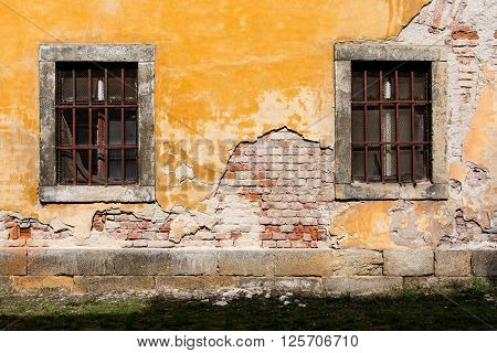 old damaged yellow plastered brick wall with barred windows and a lawn
