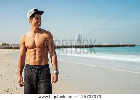 Handsome shirtless man standing on the beach.