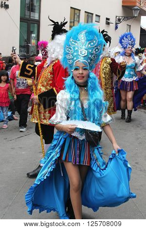 Cajamarca Peru February 7 2016: Pretty young woman with blue hair and headdress marches in Carnival Parade in Cajamarca Peru on February 7 2016