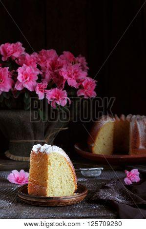 Piece of orange cake sprinkled with powdered sugar and azalea flowers on a dark background