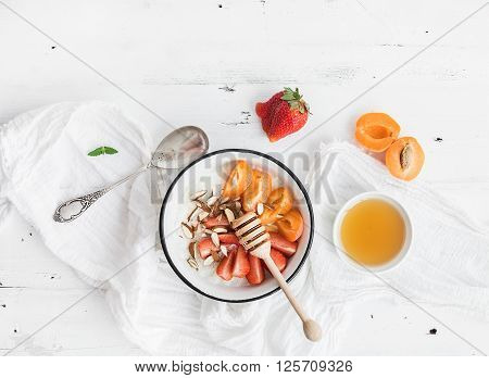 Healthy breakfast set. Rice cereal or porridge with fresh strawberry, apricots, almond and honey over white rustic wood backdrop, top view, copy space