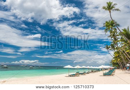 Tropical beach background from Boracay island with Beach chairs on the white sand beach with cloudy blue sky and palm trees. Travel Vacation