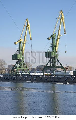 ST. PETERSBURG, RUSSIA - FEBRUARY 17, 2016: Two cranes working at the pier of the Kanonersky channel. The St. Petersburg cargo port