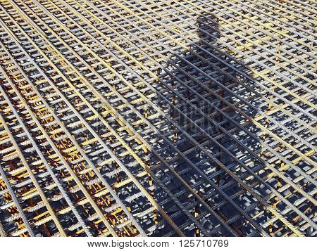The shadow of a construction worker on the rebar grids. Location shadows of the frame diagonally
