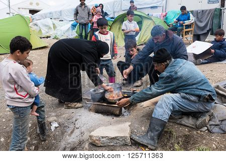 EIDOMENI, GREECE - MARCH 17, 2015: A family from Syria prepare their meal on March 17, 2015 in the refugee camp of Eidomeni, Greece. For several weeks more than 10.000 refugees and immigrants wait here for the borders to open.