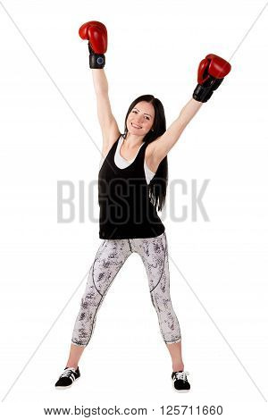 Attractive brunette girl with long hair raised his hands up in red boxing gloves. Isolated on white in studio full length