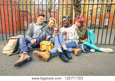 Group of happy multiracial best friends having fun using mobile smart phone - Young hipster people addicted by smartphone on social network community - Technology concept - Vivid saturated color tones