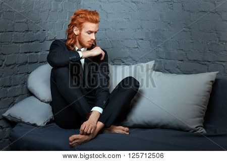 Metrosexual man with red hair and a beard sitting on a couch.