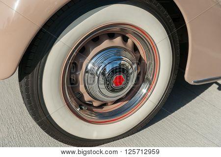 Pasadena, USA - October 4, 2015: American vintage car wheel close up shiny hubcap reflections of Packard