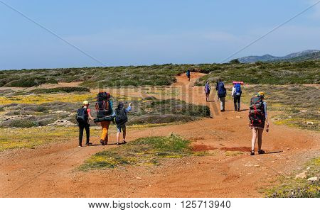 Cyprus. Akamas. Mediterranean Sea. November 24 2015. A group of tourists with large backpacks are on the sandy road to the sea
