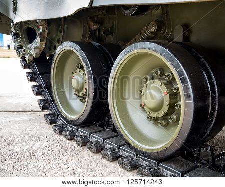 Crawler tracks of military tank and steel wheels of green color military industry modern army side view close up detail