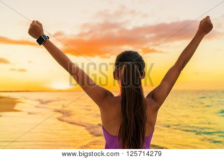 Success freedom smartwatch woman from behind at sunset. Winning goal achievement fitness athlete girl cheering on tropical summer beach wearing wearable tech smart watch activity bracelet.
