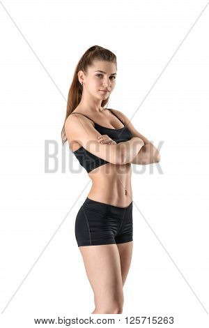 Fitness woman in shorts and a tank top standing sideways with her arms folded, isolated on a white background