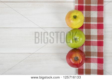 Three colored whole apples placed on red checkered kitchen tablecloth. Top view.