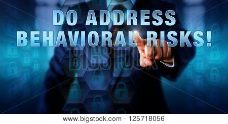 Male corporate manager is touching DO ADDRESS BEHAVIORAL RISKS! on an interactive visual screen. Business challenge metaphor and information technology concept for risks in computer usage patterns.