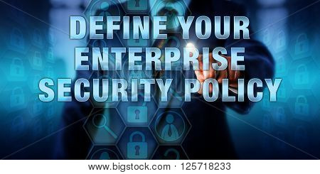Manager is pushing DEFINE YOUR ENTERPRISE SECURITY POLICY on a visual interactive display. Business challenge metaphor and information technology concept for cybersecurity standards and planning.