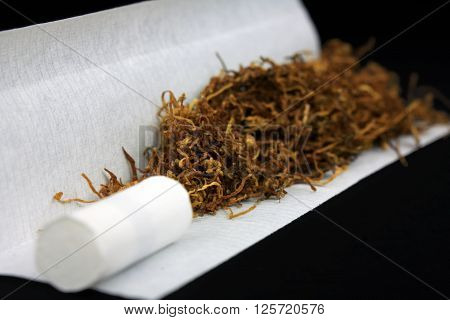 Tobacco with filter tip and paper close-up isolated on black background ** Note: Shallow depth of field