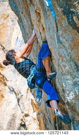 The rock-climber during rock conquest. Extreme sport