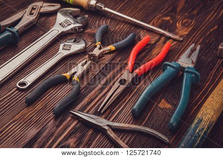 Different Working tools on a wooden table - a hammer wire cutters pliers chisels and wrenches