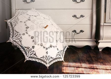 Openwork vintage umbrella against a dresser in style Provence