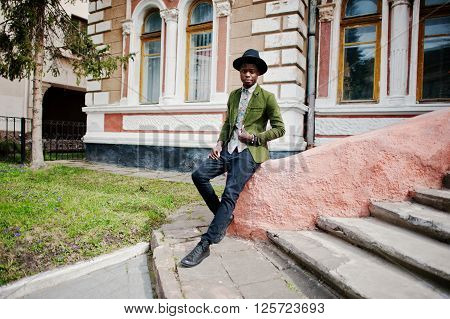 Fashion Portrait Of Black African American Man On Green Velvet Jacket And Black Hat Sit On Stairs Ba