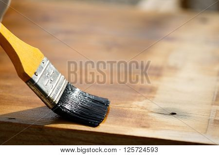 Paintbrush sliding over wooden surface protecting wood for exterior influences weathering insects and fungus. Carpentry woodwork home improvement do-it-yourself concept and background.