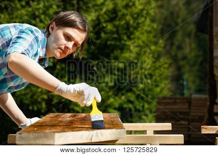 Woman applying and protecting garden furniture with fresh wood treatment paint. Outdoor protection carpentry hard at work home improvement do-it-yourself concept.