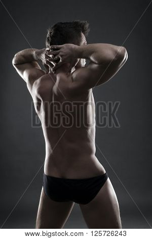 Handsome muscular bodybuilder posing on gray background. Low key studio shot. Sexy male body