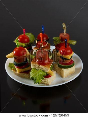 Small snacks canape with cherry tomatoes cheeze sausages and vegetables on bread on skewers on white plate against black background close up