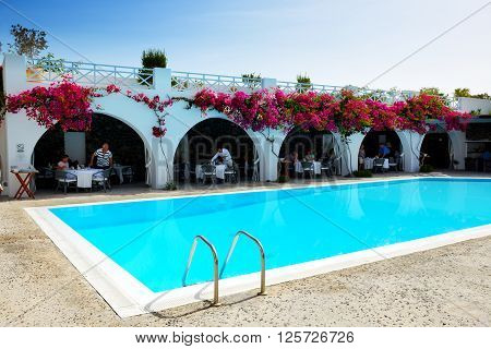 OIA GREECE - MAY 19: The tourists enjoying their vacation at luxury hotel on May 19 2014 in Oia Greece. Up to 16 mln tourists is expected to visit Greece in year 2014.