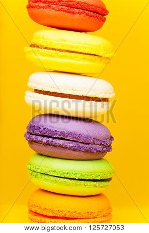 Sweet and colorful French dessert macaron standing on each other on yellow background