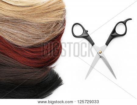 Hairdresser's scissors with varicolored strands of hair, isolated on white
