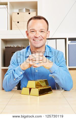 Happy business man with investment in gold bars in office