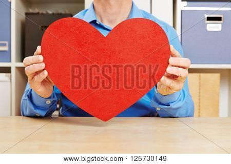 Man in love holding big red heart in office on his desk