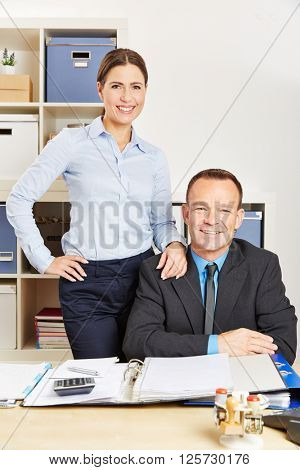 Two smiling colleagues at the desk in a company office